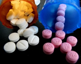 White and pink pills with pill vials on black background