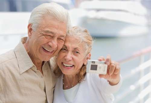 Senior Couple Using Digital Camera at Marina --- Image by © Royalty-Free/Corbis