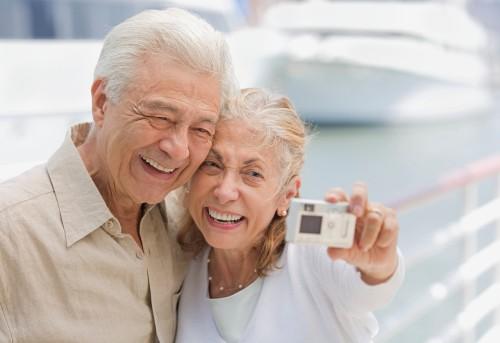 Senior Couple Using Digital Camera at Marina --- Image by © Royalty-Free/Corbis